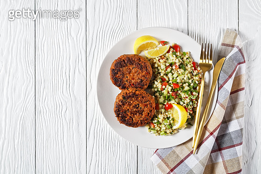 harissa lamb burgers served with pearl couscous salad on a plate with lemon slices on a white wooden table with golden cutlery, horizontal view from above, flat lay