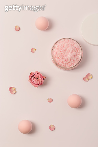Aromatic crystals of sea salt with essential oil flower of rose. Spa composition with cosmetic bathroom product top view