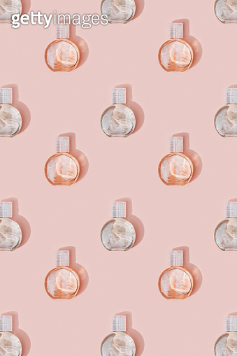Beauty products mock up. Pattern from small bottle with transparent gel on pale pink background. Skincare, body treatment concept.