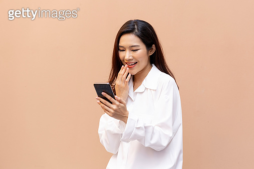 Portrait of an Asian woman, healthy skin. She reads content from a smartphone. She follows the news on her cell phone. She video calls people in the family.