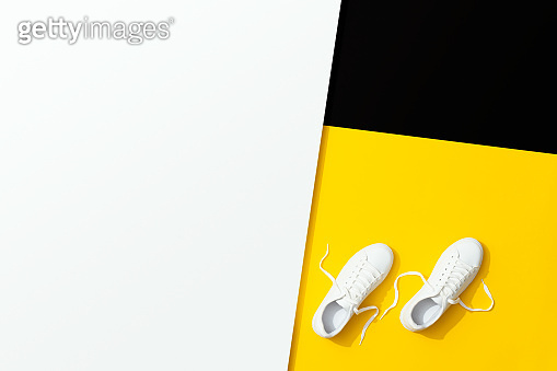 White sneakers on black, white and yellow background