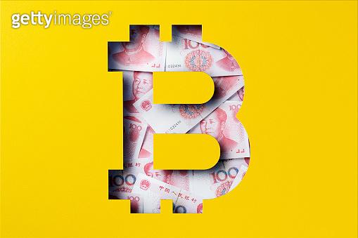 Chinese yuan heap under paper cutout, Bitcoin icon