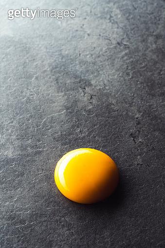 Egg yolk on black background