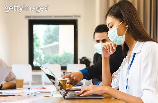 Group of young asian entrepreneurs discussing.Asia young businesspeople brainstorming meeting working together sharing data and glass wall with face mask work after corona virus.