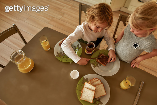 Top view of two little kids preparing breakfast for themselves in the kitchen. Cute brother spreading chocolate butter on toasted bread
