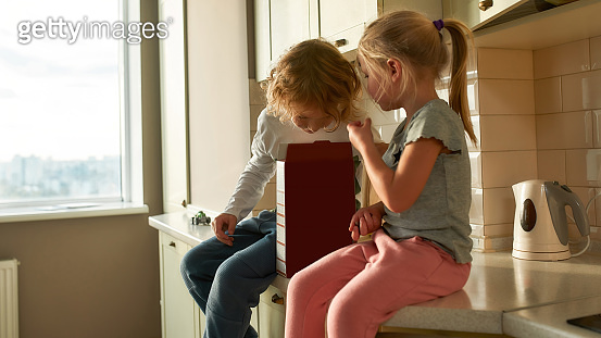 Portrait of two joyful kids, brother and sister eating cornflakes while sitting together on the kitchen cabinet at home