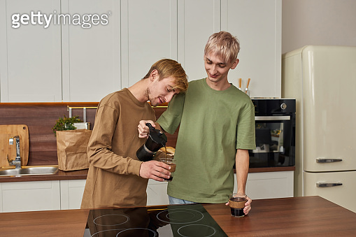 Cheerful homosexual pair pouring coffee into cups