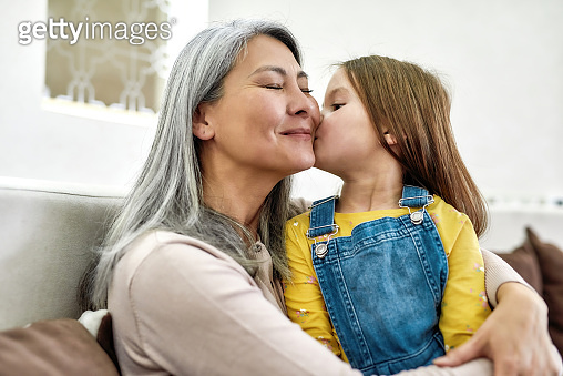 Portrait of cute little preschool granddaughter kissing her grandmother while spending time together at home