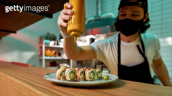 Professional sushi chef wearing protective mask and gloves adding sauce while preparing sushi rolls at commercial kitchen