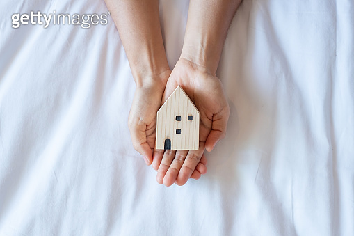 Hands holding house model on white background with copy space. Financial, money, refinance, Real estate and new home concept