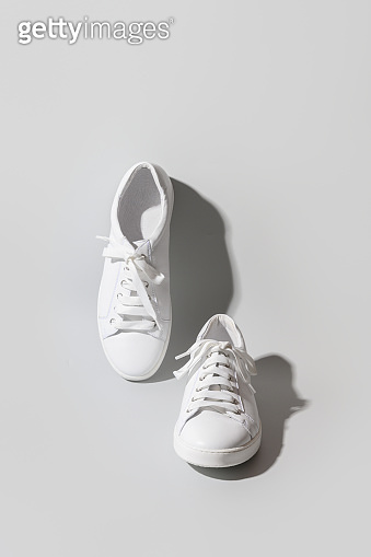 White women's new gumshoes or sneakers on grey.