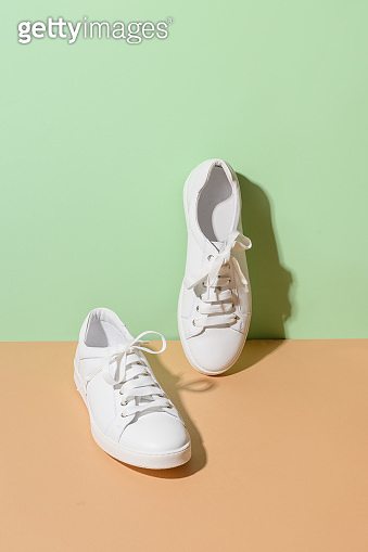 White female gumshoes on a beige background.