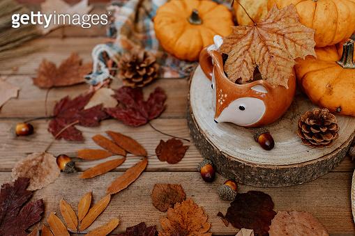 Autumn creative composition made of pumpkins, tea cup, dried leaves. Autumn, fall, halloween concept. Season background