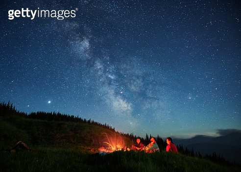 Recreation under night full starry sky in the mountains.