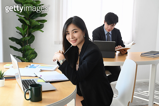 Happy businesswoman smiling to camera while siting with her colleague in office.