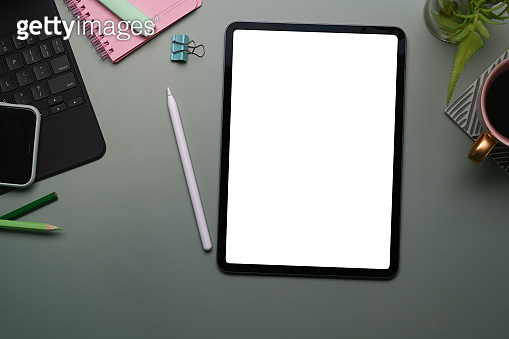 Top view of mock up digital tablet with white screen, smart phone, stylus pen and notebook on gray background.
