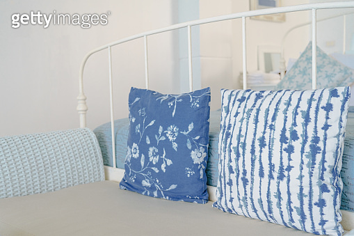Vintage white bedroom with blue and white color pillows.
