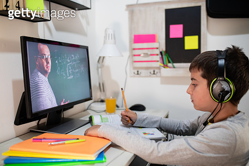 Distance learning, a boy in headphones sits at a table at home. The concept of online education, home education, technology, school