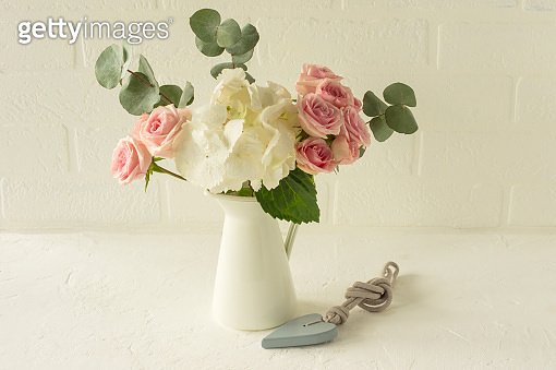 bouquet of Roses, Hydrangea and eucalyptus in a white jar on a table. Flowers composition for interior decoration.