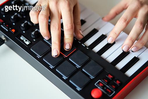 Woman playing a small modern music synthesizer