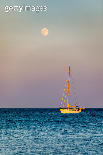 Full moon rising over the water with a small sailing boat in the foreground. Sailing boat with raising moon at sunset. Moon rising over the sea and yacht floating on the water surface. Sardinia, Italy
