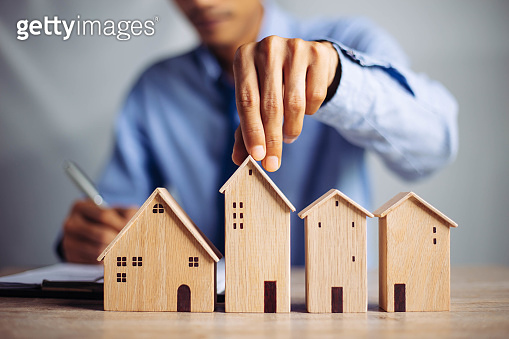 Businessman choosing mini wood house model from model on wood table, Planning to buy property. concept of Choose the best.