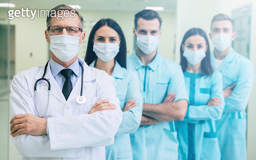 Serious confident doctors team in safety medical masks with crossed arms are looking on the camera on hospital background