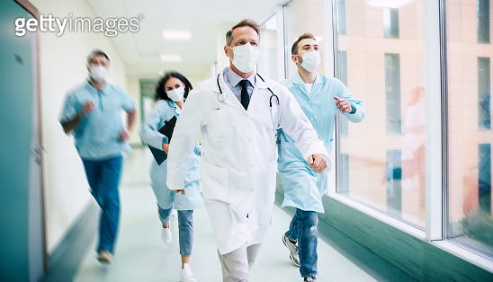 Group of serious and confident doctors in safety medical masks are running fast on the hospital for an urgent sick patient