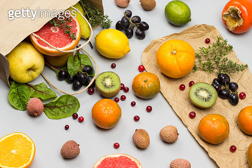 Fruits in paper bag. Persimmon, kiwi and orange on table.