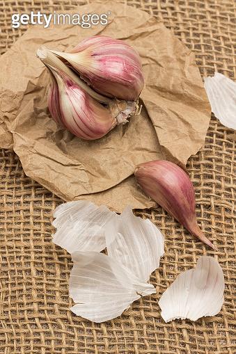 Head of garlic and clove on sacking.