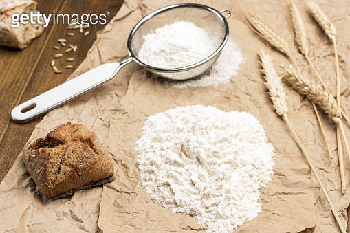 Flour, spikelets of wheat, bread and sieve on brown paper