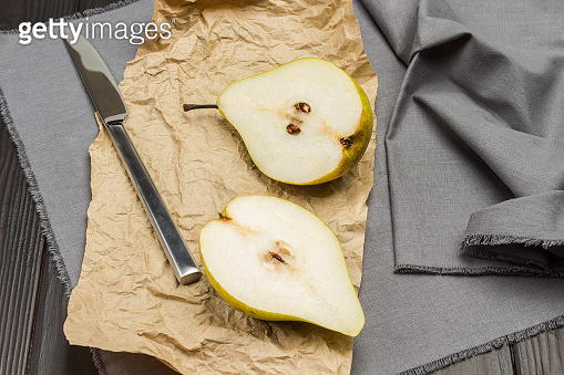 Two halves of pear on paper and gray napkin.