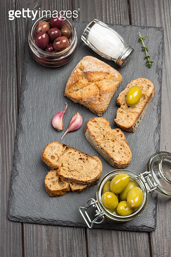 Green olives and slices of bread. Olive oil in glass jar and thyme sprigs.