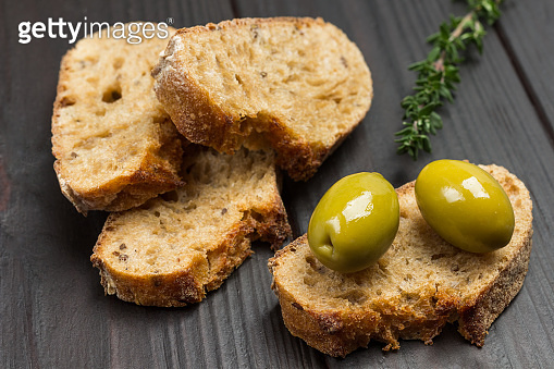 Green olives and slices of bread.