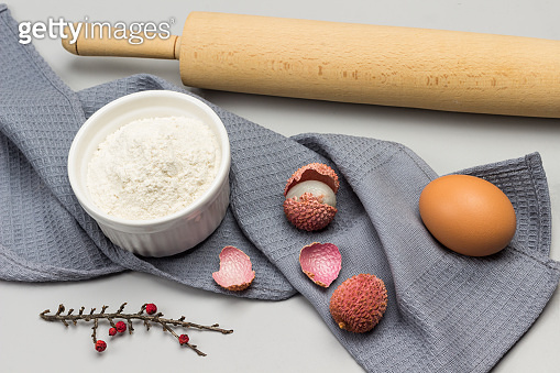 Egg and bowl of flour on gray napkin. Rolling pin.
