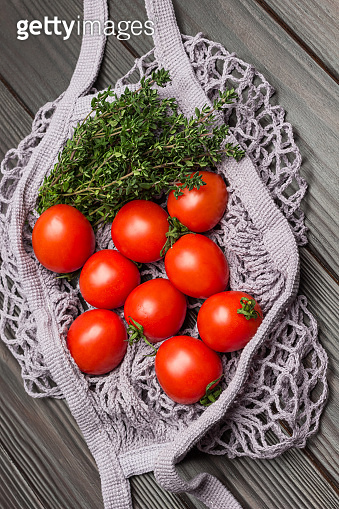 Red tomatoes and thyme twigs in natural reusable mesh bag.