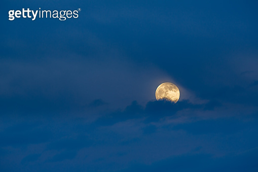 Mystery full moon behind the clouds during blue hour