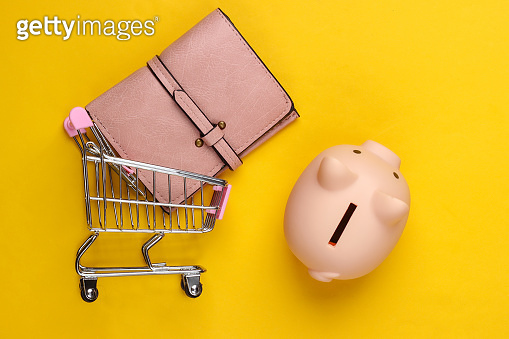 Shopping concept. Piggy bank and wallet, supermarket trolley on yellow background. Minimalistic studio shot. Overhead view. Flat lay.
