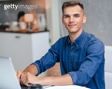 male freelancer works on a laptop in his kitchen