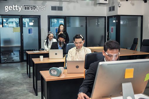 Group of young asian colleagues working with laptop at desk in modern office. Female manager consulting with employee