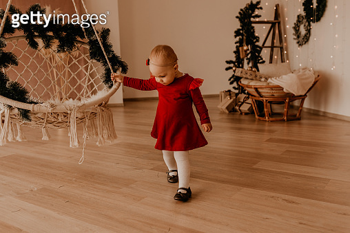 child stands at white wall with garlands Christmas tree with wrapped gifts