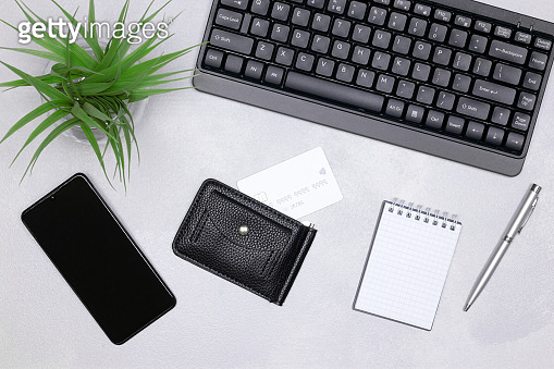 Shopping list, Internet shopping, online payments concept. Keyboard, smartphone, credit card inside wallet, open blank notebook on the desk, top view
