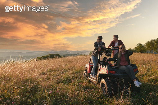 group young happy people enjoying beautiful sunny day while driving a off road buggy car