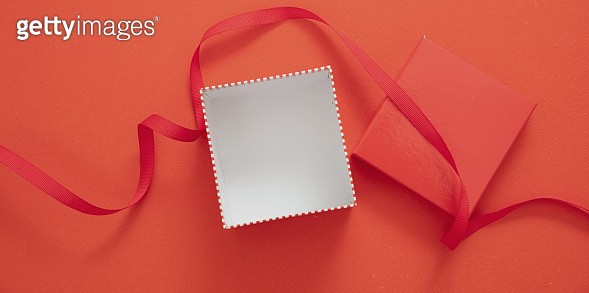 Christmas present concept. Gift box open and empty on red background.