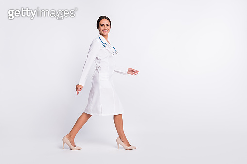 Full length photo of confident cute young woman therapist wear formal coat walking empty space isolated white color background