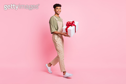 Full length photo portrait of african american man walking carrying present isolated on pastel pink colored background
