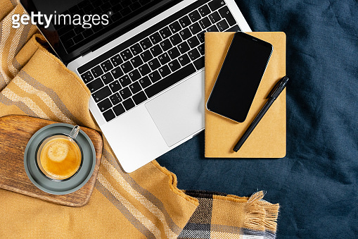 Work at home concept. Laptop with black keyboard, beige notebook, pen, mobile phone, cup of coffee and plaid on blue blanket.