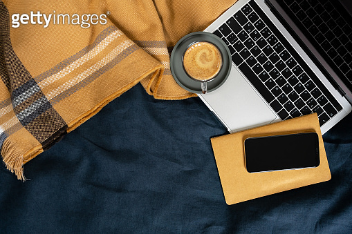 Laptop, mobile phone, notebook and cup of coffee on the bed with yellow plaid and blue blanket.