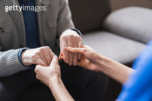 Woman nurse hold hand of elderly grey-haired man showing care and bond close up, female doctor in white coat talk with aged patient sitting together indoor, concept of support, caregiving and nursing service