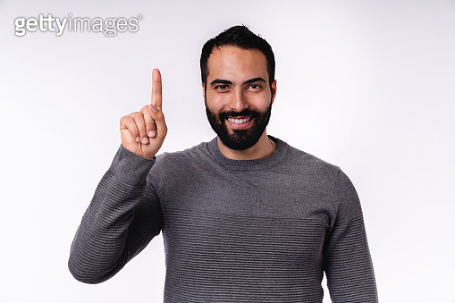 Attractive smiling arab man in casual attire pointing at copy space isolated over white background